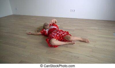 Cute blond girl in dancer dress lying on floor and dance....