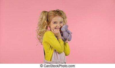 Cute blond girl is hugging her teddy-bear - Cute curly blond...