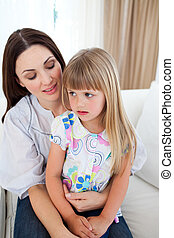 Cute blond girl sitting on her mother\'s lap