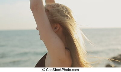 Cute blond girl with long hair wearing a black dress enjoying near the sea at sunset