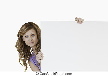 Cute blond-haired woman holding a white board