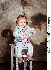 Cute blond little girl sitting on white chair and holding her toys. Studio portrait on brown grunge background