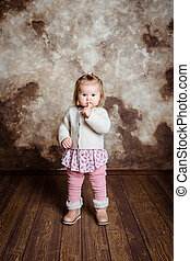 Cute blond little girl with big grey eyes and plump cheeks