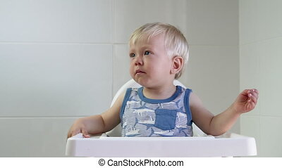 Cute blond toddler boy coughing in high chair - Toddler...