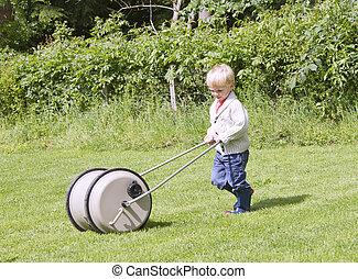 Cute blond toddler pushing water barrel