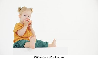 Cute blonde baby girl eats apple against white background