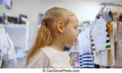 Cute blonde baby girl in toy's store for children