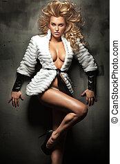Cute blonde beauty posing in white fur
