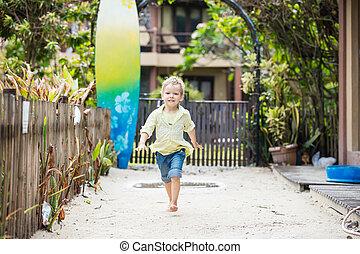 Cute blonde boy walking barefoot