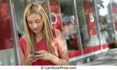 Cute blonde chatting with her friends using phone on the street
