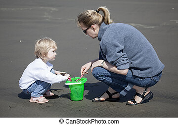 Cute Blonde Child and Her Mother Playing at the Beach - Cute...