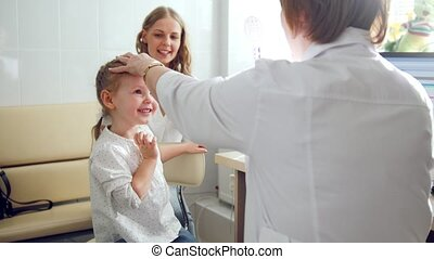 Cute blonde girl with mommy in child's ophthalmology -...