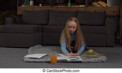 Cute blonde school girl doing her homework