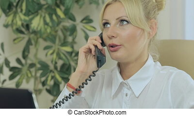 Cute blonde talking on the phone in office