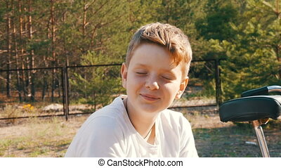 Cute blonde with blue eyes a teenager boy sits and smile in...