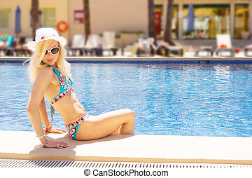 cute blonde woman by the swimming pool