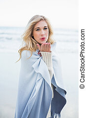 Cute blonde woman in a blanket blowing a kiss to the camera