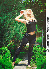 cute blonde woman in black outfit enjoys the sun