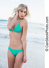 Cute blonde woman in green bikini posing looking at camera