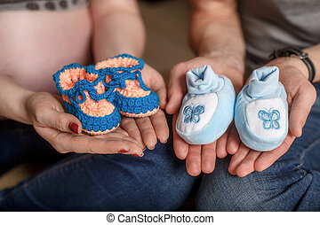 Cute blue knitted baby booties on hands. Pregnancy concept