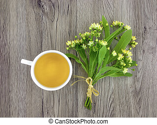 Cute bouquet of linden flowers and tea cup on wooden table....