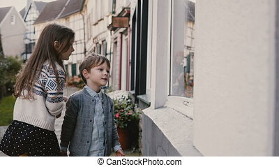 Cute boy and girl choose gifts at toy storefront. Two Caucasian children stand window shopping. Hattingen, Germany. 4K.