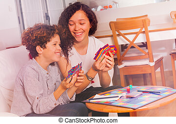 Cute boy and girl having fun playing tabletop game