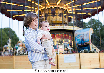 Cute boy and his baby sister enjoying amusement park
