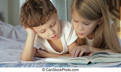 Cute boy and his sister  reading book