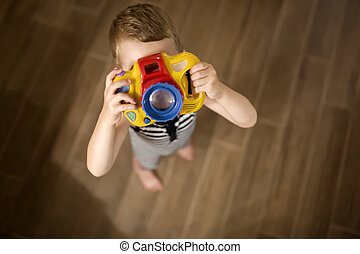 Cute boy becoming photographer