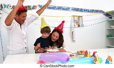 Cute boy blowing out candles for his birthday