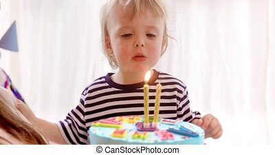 Cute boy blowing two candles on a cake. Birthday