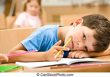 Close-up of tired pupil with yellow crayon putting his head on arm and looking at camera