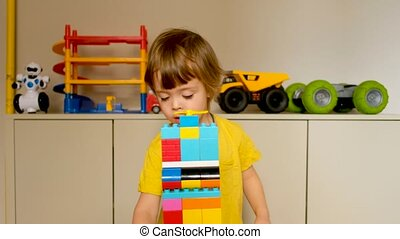 Cute boy demonstrates a tower toy made of blocks and talks about it for the Internet