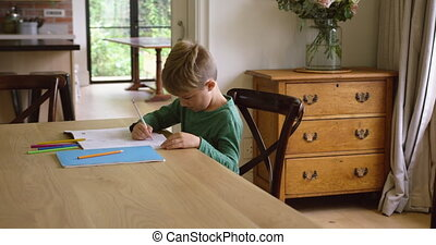 Cute boy doing homework at dining table in a comfortable ...