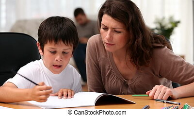 Cute boy doing homework with his mother in the living room