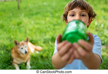 Cute boy drinking from a bottle, dog watching in the background