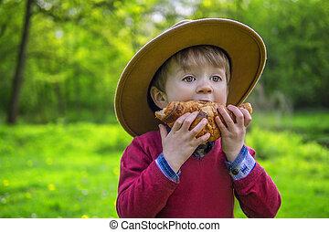 Cute boy eating a croissant