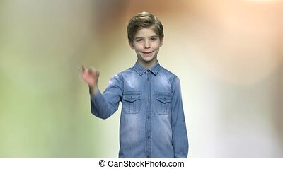 Cute boy giving OK sign. Portrait of handsome child in denim jacket showing okay gesture with fingers. Abstract blurred background.