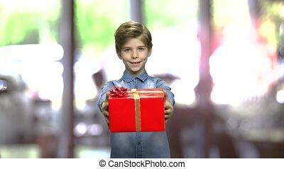 Cute boy handing red gift box.
