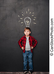 Cute boy having an idea over chalkboard background with drawings