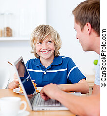 Cute boy having breakfast while his father using a laptop