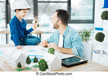 Cute boy having chat with father at his work
