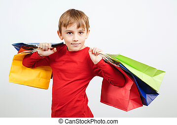 Cute boy holding shopping bags. Little shopper standing over white background. Holidays sales and discounts.