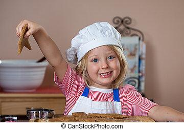 Cute boy holding up gingerbread man