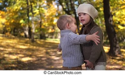 Cute boy hugging sister with down syndrome outdoor