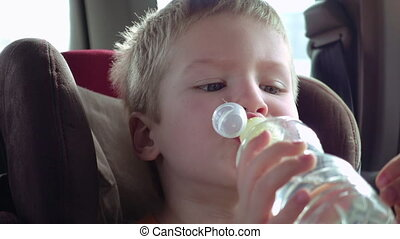 Cute boy in a child car seat drinks of water