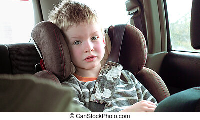 Cute boy in a child car seat