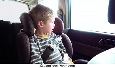 Cute boy in a child car seat looks out the window