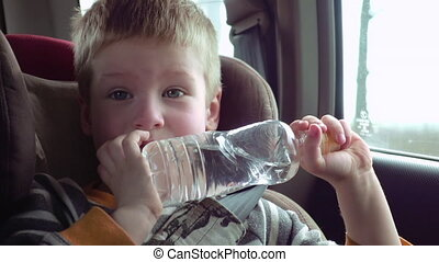 Cute boy in a child car seat with bottle of water